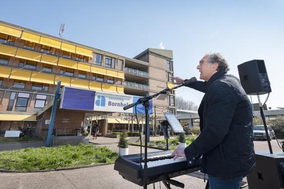 Aristakes zingt voor deur verpleeghuis Hoofddorp, applaus achter de ramen van Bornholm