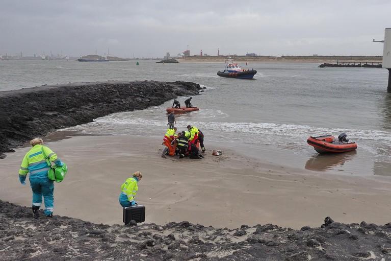 Omstanders redden man die hond achterna springt uit water bij Zuidpier in IJmuiden aan Zee